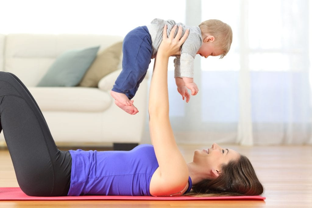 Side view portrait of a happy mother exercising raising her baby on the floor at home